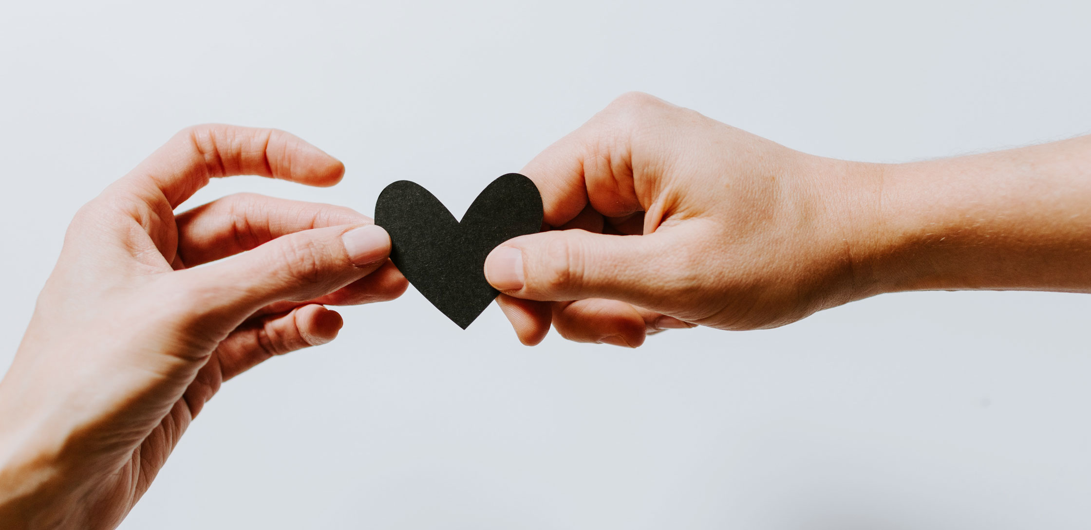 Holding black paper heart in two hands