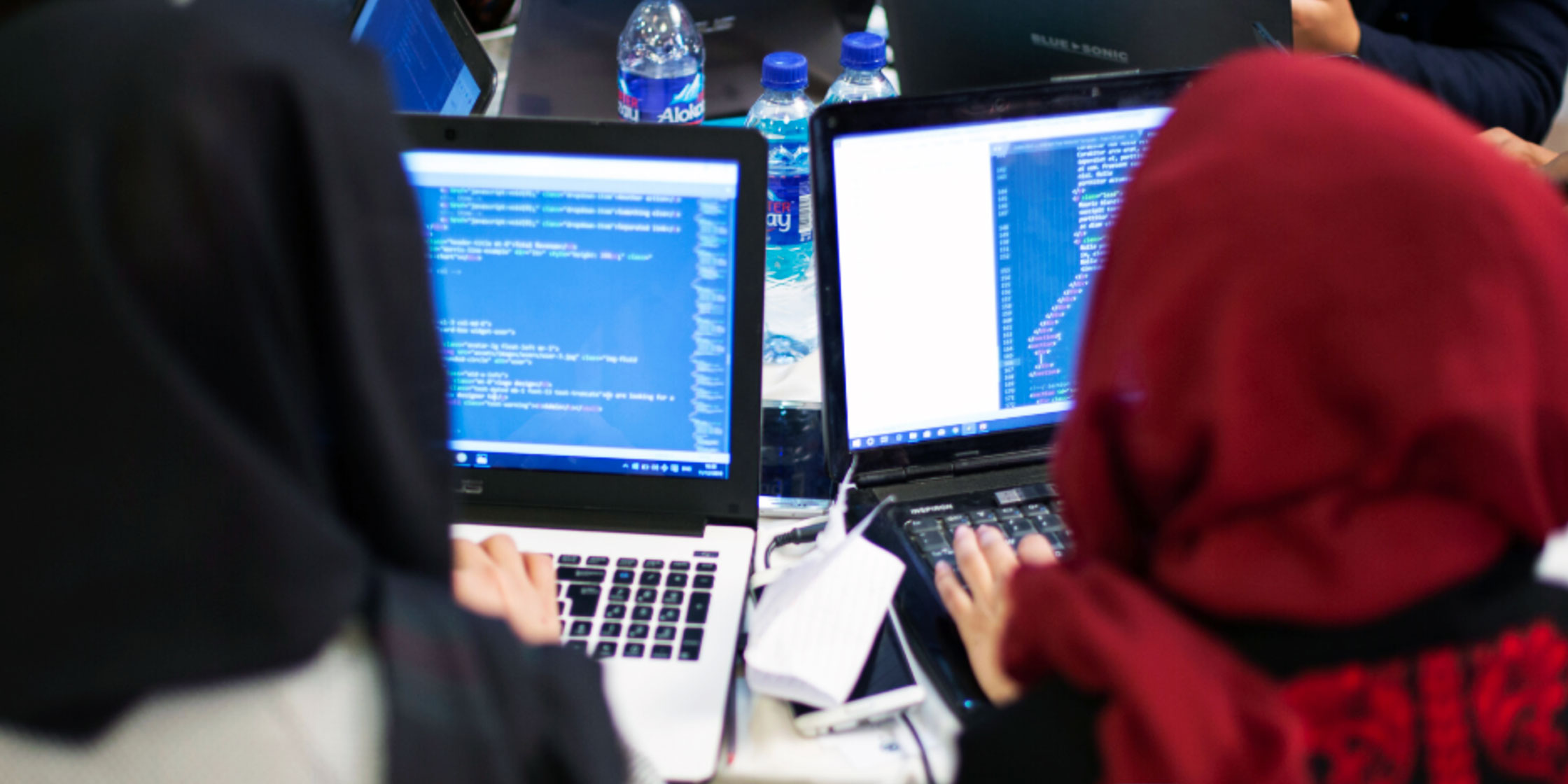 Two women wearing hijab are working at their laptops